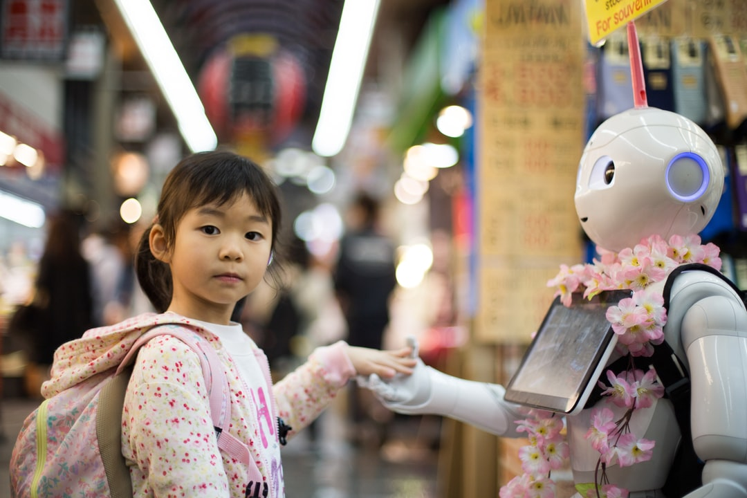 A little girl standing next to a toy